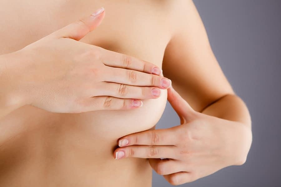 Mulher fazendo auto exame de cancer de mama