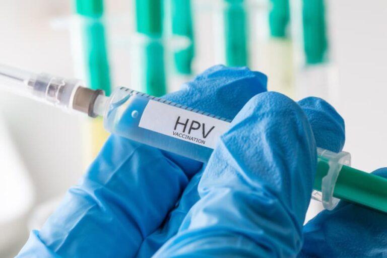 Médico com luvas segurando seringa com vacina contra HPV