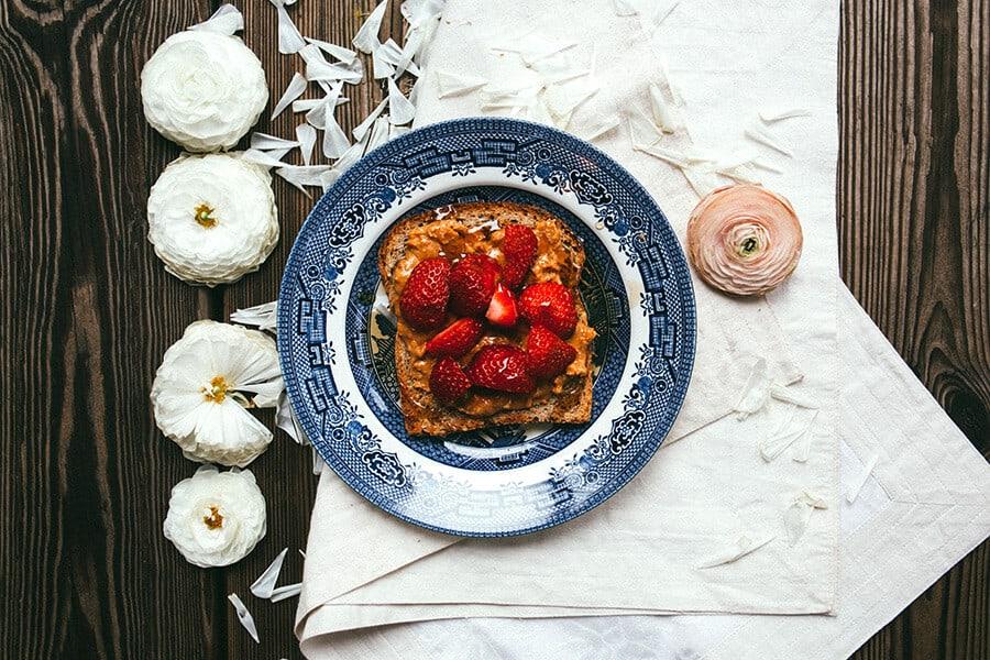 Prato com sobremesa de torrada com doce de leite e morangos