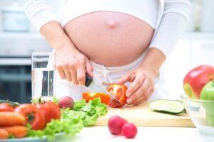 Mulher grávida preparando alimentos saudáveis