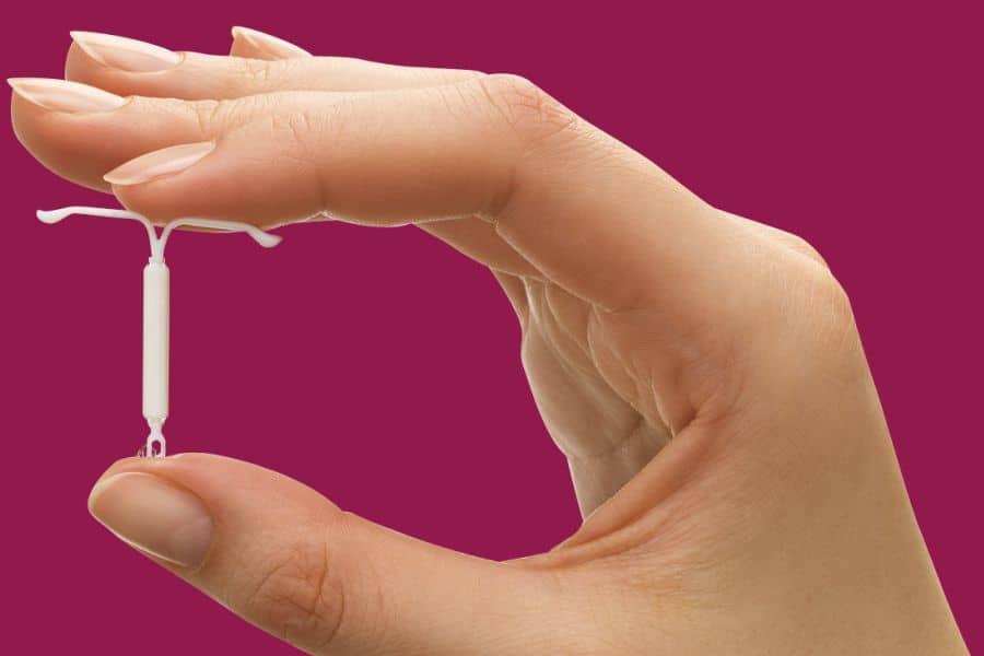 Mulher segura um Diu Mirena entre os dedos