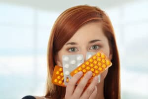 Mulher jovem segurando diversos tipos de anticoncepcionais