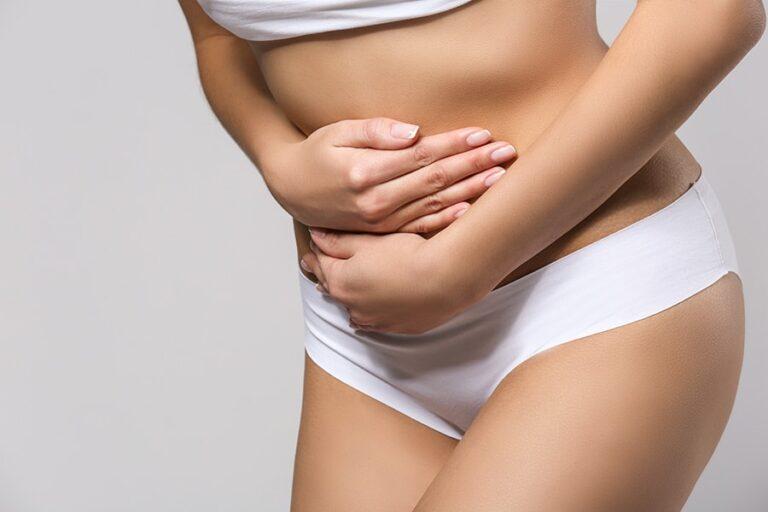 Mulher com mãos no abdomen expressando a dor da endometriose