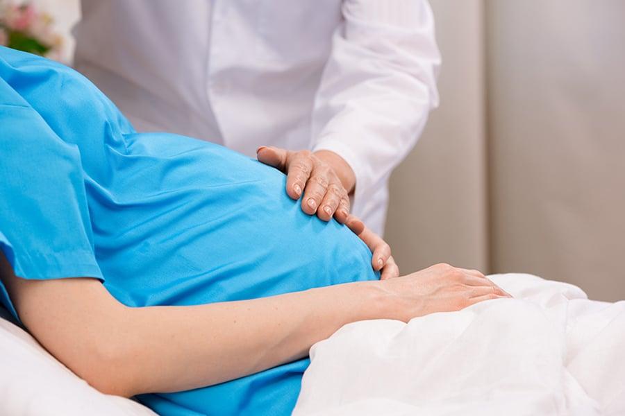 Obstetra examina a barriga de uma gestante