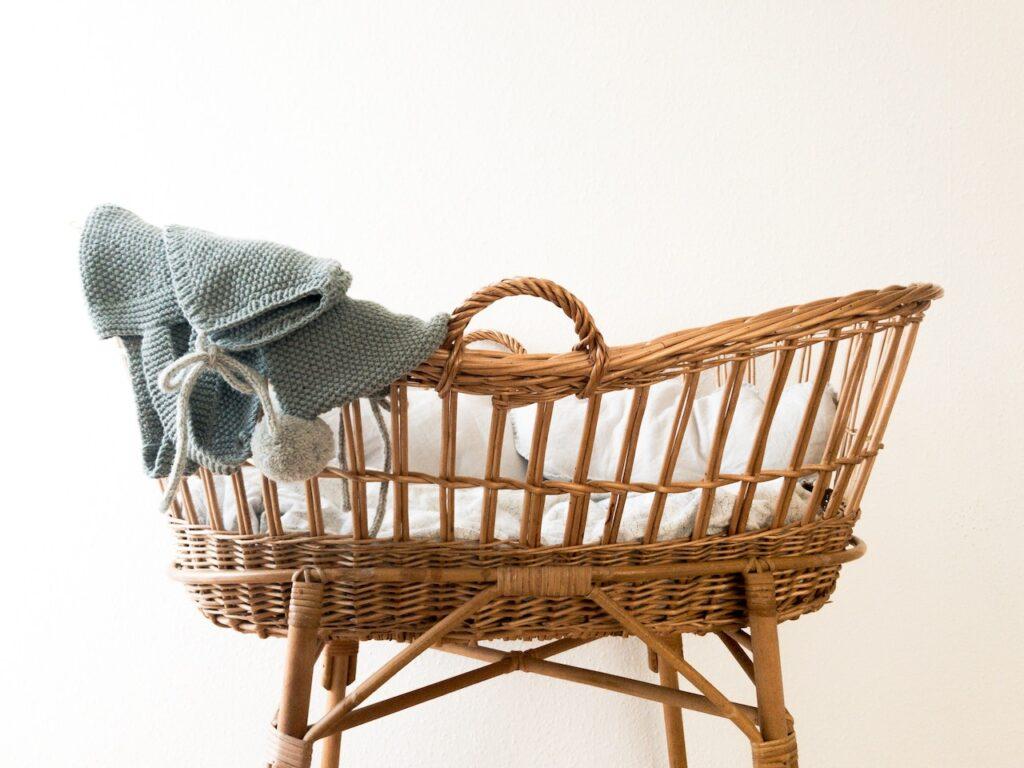 Berço vazio em forma de cesto de vime com pés e decorado